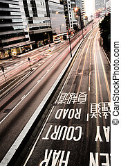 It is traffic with cars motion blurred and mark on the ground in Hong Kong.