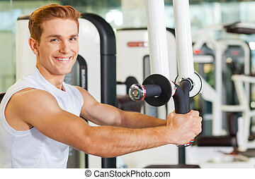 It is very important to stay fit. Handsome young man working out in gym and smiling