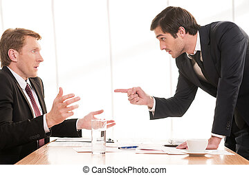 It is your fault! Two young men in formalwear arguing while one of them pointing his opponent