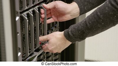 It engineer or technician working with a blade server in data rack. Shot in enterprise datacenter. Camera movement.