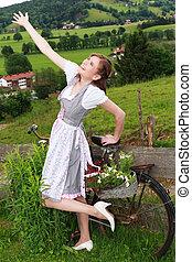 It radiates pure joy - Bavarian Girl in Dirndl leans on a...