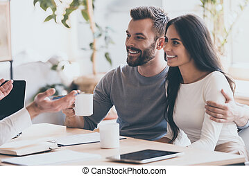 It seems to be a good proposition. Cheerful young couple bonding to each other and smiling while looking at some man sitting in front of them and gesturing