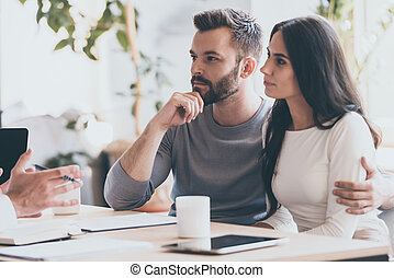 It seems to be a good proposition. Concentrated young couple bonding to each other and listening to some man sitting in front of them
