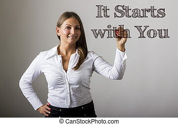 It Starts with You - Beautiful girl writing on transparent surface