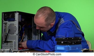 IT support engineer changes the hard drive of desktop computer