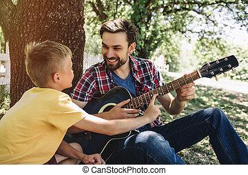 it., wants, あごひげを生やしている, happy., 男の子, これ, guitar., ギター, プレーしなさい, son., 父, leeaning, 顔つき, 保有物, 小さい, 微笑, 人, 彼
