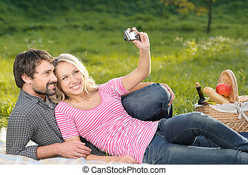 It will be the great shot. Loving young couple taking the photographs of themselves on summer picnic