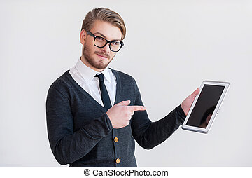 It will make your life easier. Handsome young man in glasses holding a digital tablet and pointing it while standing against grey background