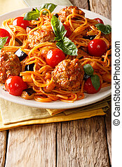 Italian American pasta spaghetti with meat balls, vegetables in a tomato sauce close-up on a plate on a table. vertical