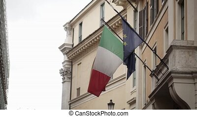Italian and EU flag at cloudy day