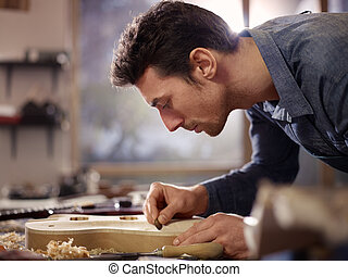 mid adult man at work as craftsman in Italian workshop with guitars and musical instruments, smoothing guitar body