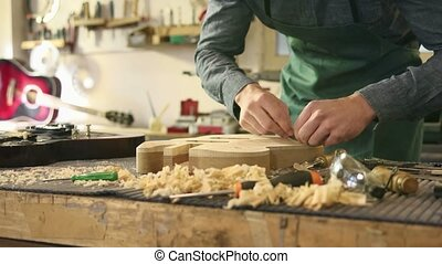 italian artisan works as lutemaker - mid adult man at work...