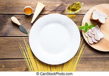 Italian carbonara ingredients with empty plate on wooden background