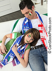 Italian couple on couch waiting for soccer match