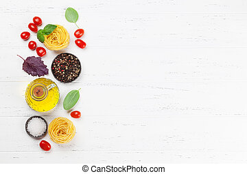 Italian cuisine. Basil, tomato, pasta and spices cooking. Top view with space for your recipe