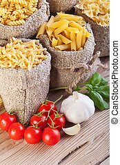 Italian cuisine concept with pasta variety in burlap bags and seasoning ingredients