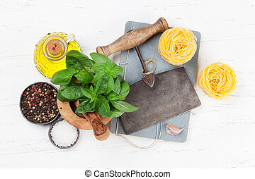 Italian cuisine. Pasta, basil, olive oil and spices cooking. Top view