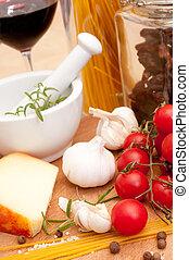 Italian Cuisine - spaghetti, tomatoes, dried tomatoes, pecorino cheese, garlic, rosemary in mortar, salt and glass of red wine
