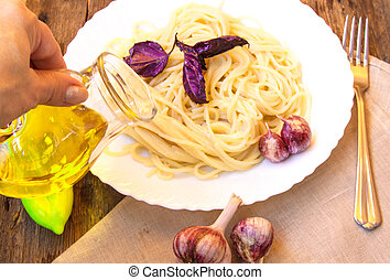 Italian cuisine, spaghetti with Basil and garlic, a woman's hand holding a glass jug of olive oil