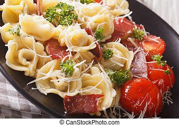 Italian cuisine: tortellini with ham, tomatoes and parmesan close-up. horizontal