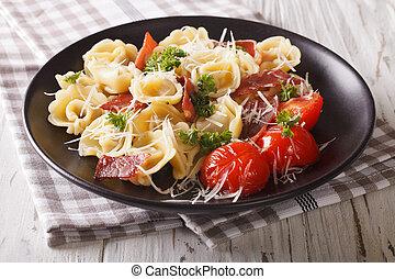Italian cuisine: tortilini with ham, tomatoes, herbs and cheese closeup. horizontal