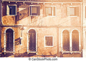 Italian culture on Venetian facades at dawn in a contemporary style. Venice is rich and poor, well-groomed and abandoned, reflected in its windows.