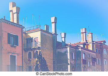 Italian culture on Venetian facades in faded color effect. Venice is rich and poor, well-groomed and abandoned, reflected in its windows.