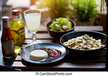 Italian dinner with pasta, panakota and salad on wooden...