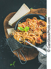 Italian dinner with meatballas, basil and parmesan cheese pasta