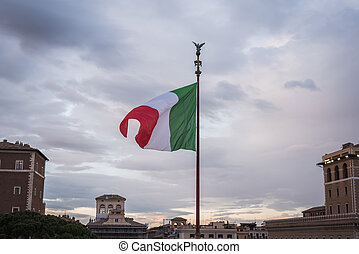 Italian flag floating on the monument Vittorio Emanuele II in Rome