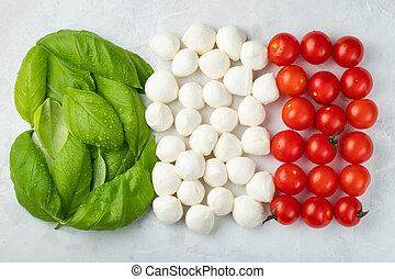 Italian flag made with Tomato Mozzarella and Basil. The concept of Italian cuisine on a light background. Top view with. Flat lay