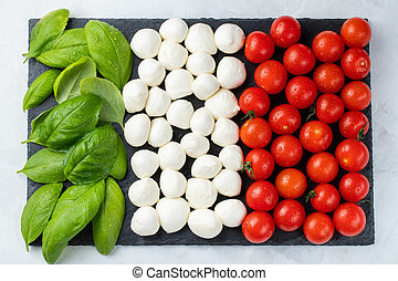 Italian flag made with Tomato Mozzarella and Basil. The concept of Italian cuisine. Top view. Flat lay
