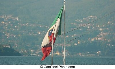 Italian flag on Stresa background. Flag, water and town.