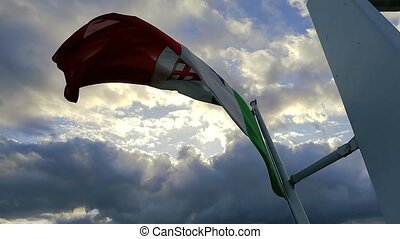 Italian flag waving in the wind at sunset