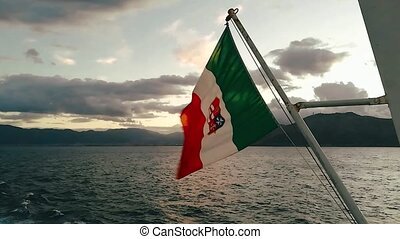 Italian flag waving in the wind at sunset at sea