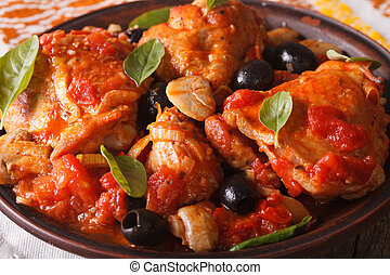 Italian food: Chicken Cacciatori with basil on a plate close-up. horizontal