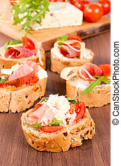 Fresh homemade crispy Italian antipasto called Bruschetta topped with tomato, garlic and basil on wooden board (Selective Focus, Focus on the tomato piece in the front)