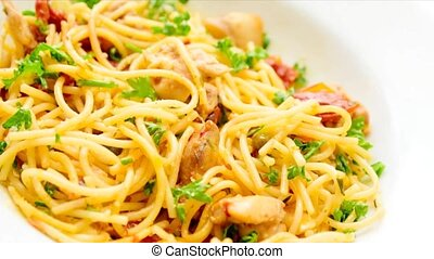 Italian spaghetti with sun-dried tomatoes, chicken meat, parmesan sprinkled with parsley. Camera pans right.