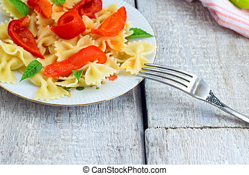 Italian food. Pasta fusilli with tomato sauce, peppers and basil on wooden background.