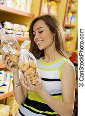 italian food - woman in a supermarket reading nutrition...