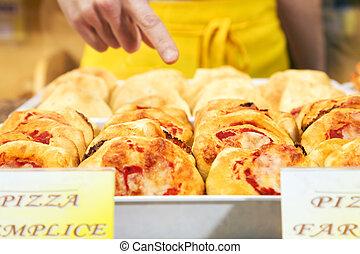italian food - sales clerk in a supermarket pointing a slice...
