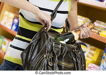 italian food - woman in a supermarket stealing a bottle of...