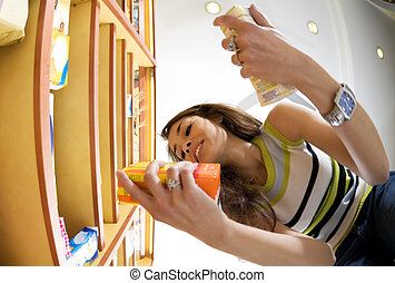 italian food - woman in a supermarket reading nutrition ...