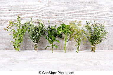Italian herbs in bundle on white wooden background