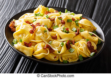 Italian homemade tortelloni served with bacon and cheese close-up in a plate. horizontal