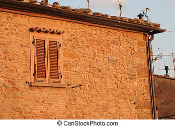 Italian house in Tuscany with antennas, in the evening sun