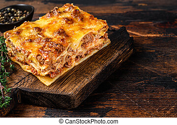 Italian Lasagna with bolognese sauce and mince beef meat. Dark Wooden background. Top view. Copy space