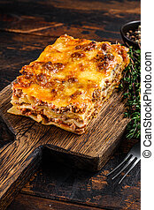 Italian Lasagna with bolognese sauce and mince beef meat. Dark Wooden background. Top view