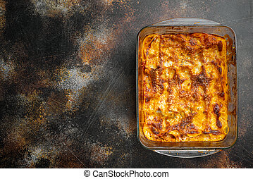 Italian Lasagne with tomato bolognese sauce and mince beef meat, in baking tray, on old dark rustic background, top view, flat lay, with copy space for text