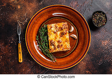Italian Lasagne with tomato bolognese sauce and mince beef meat on a rustic plate. Dark background. Top view